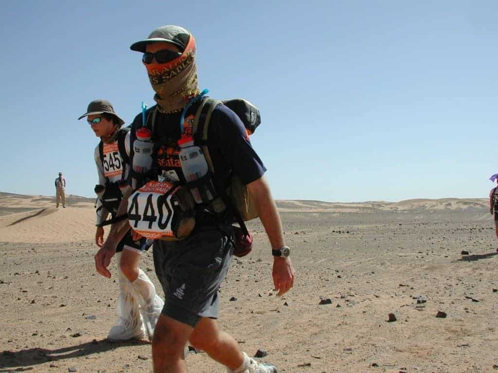 A side shot landscape photo of two people walking in the desert. They are participants of the Marathon Des Sables. A man in the centre is wearing a Original Buff® as face mask. A woman in the back is wearing a Original Buff® as neck cooler. It looks as if it is the end of the race and everybody is tired. The woman in the back is looking weak. The man in font still seems to have energy left. The photo was taken in 2003. Today the correct product for this race is the High UV Buff®. Source: buff.eu © Distributed for the promotion of the Original Buff® in outdoor / adventure