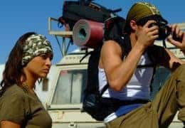 A side landscape shot of a woman and a man in front of a 4WD. The woman is wearing a High Uv Buff® as alice band. The man is wearing a Cap Buff®. It looks as if they are travelling and on an adventure. Photoshoot for Buff® summer catalogue with models. Source: buff.eu © Distributed for the promotion of the High UV Buff® in outdoor / adventure