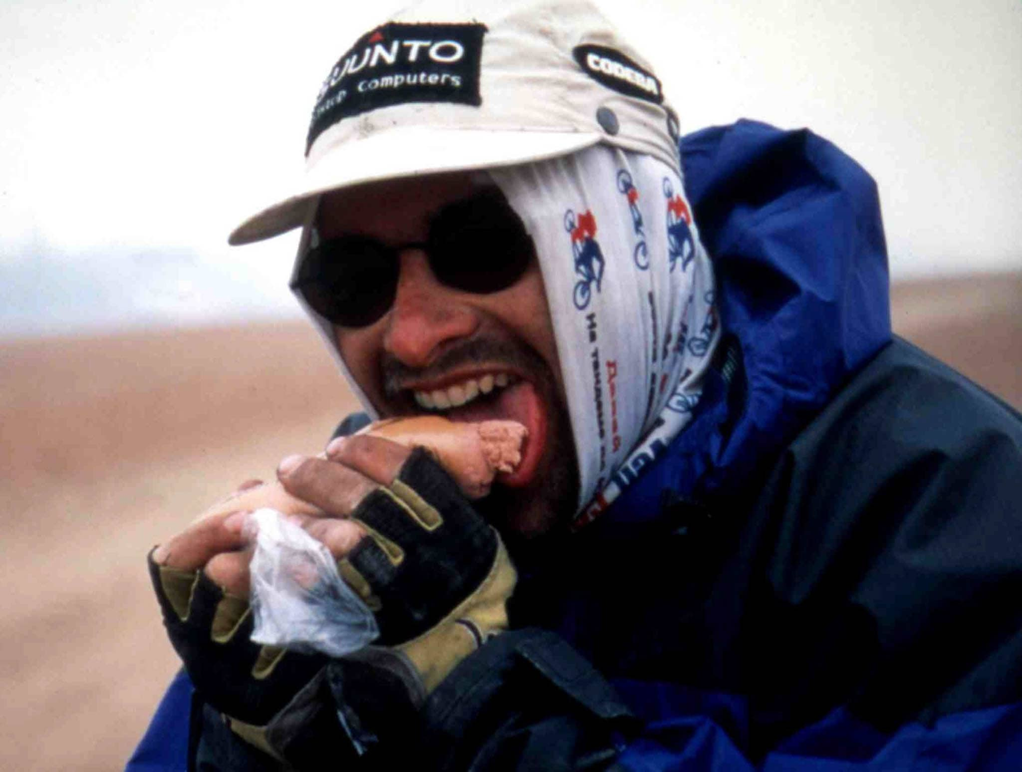 Cyclist on an adventure. Wearing a Original Buff® as balaclava. Eating something. (buff.eu)
