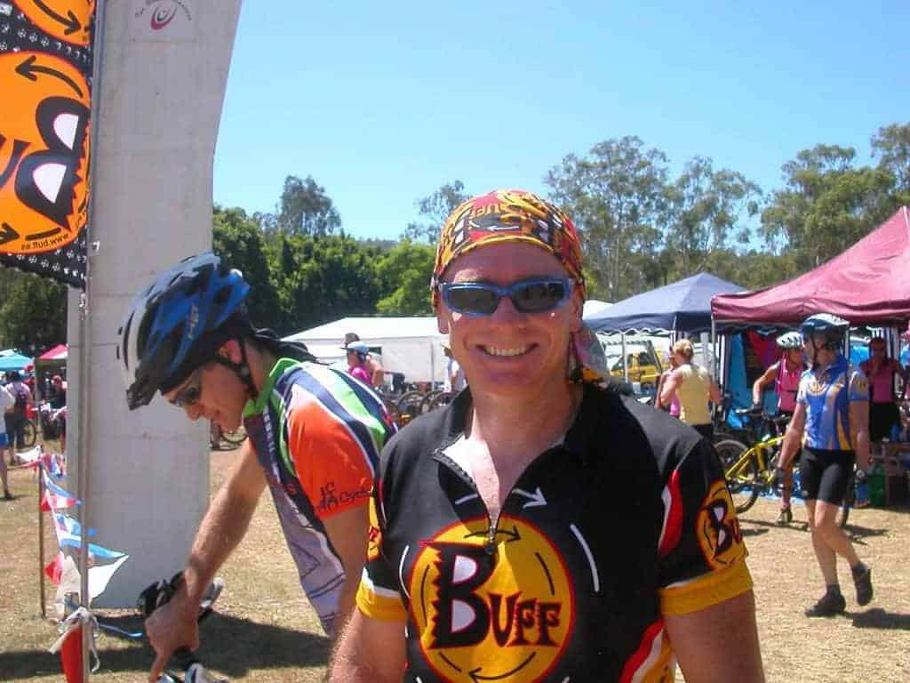 Landscape frontal shot photo of a male mountain bike rider. Scott smiling into the camera at the 2005 24 hour mtb race in Kooralbyne. It is hot. He is wearing a Original Buff® as helmet liner to cool the heat down. Source: Edward Copyright: ©2004 Buff Downunder Pty Ltd