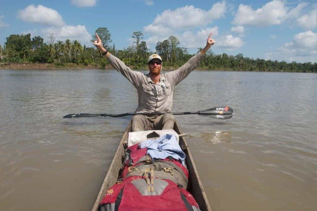A frontal shot landscape photo of a man in a canoe raising his arms as a sign of victory. It is Andrew Johnson on the Sepik River in Papua New Guinea. He is wearing a Visor® Buff® as legionnaire style cap. The scene looks hot & humid. Image taken during the first spring to sea traverse of the Sepik River in Papua New Guinea. Source: Clark Carter © Clark Carter. http://www.adventureplaybook.com/