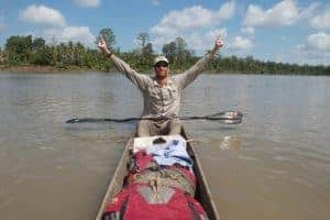 Andrew Johnson on the Sepik River in Papua New Guinea. He is wearing a Visor® Buff® and raising his arms in a victory pose. Image taken during the first source to sea traverse of the Sepik River in Papua New Guinea. © Clark Carter. http://www.adventureplaybook.com/