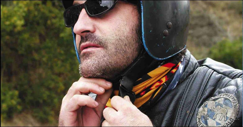 A side landscape shot of a man tying his motorcycle helmet. Visible is his upper body with the top of his helmet not visible. He is wearing a motorcycle leather jacket and a Original Buff® as scarf. His helmet is matt black and he is also wearing black sunglasses. He looks like a Harley rider. Interesting in this photo is how nice the Buff® closes up the jacket. It fills out all the nooks and crannies. The weather looks classic European summer. Not hot & not cold with a slight chill in the morning. Source: buff.eu Copyright: Distributed for the promotion of the Original Buff® in motorcycle