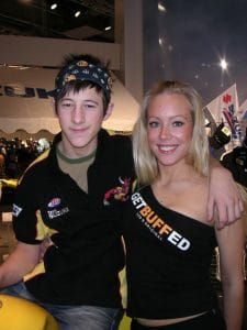 A portrait frontal upper body photo of a you man and woman on a motorcycle trade show. The man on the left is sitting on a motorbike and the woman is standing to the right. The woman seems to be a promo girl for Buff® and the man seems to be a Suzuki team rider. He is wearing a Original Buff® as head band in a very stylish, expressive way. Source: buff.eu Copyright: Distributed for the promotion of Original Buff® in motorcycling