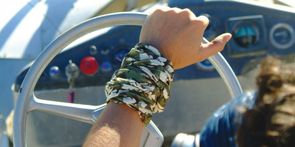 Man driving a car. Photo is taken from behind. It shows the left arm holding the steering wheel. A High Uv Buff® as wristband is the main element. Photoshoot for Buff® summer catalogue with models. © Original Buff S.A