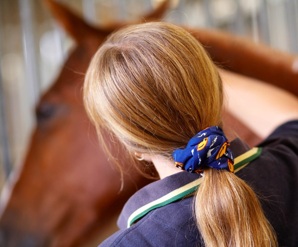 A back landscape shot of a woman with long hair combing a horse. The focus is on her long hair held together by a Original Buff® as scrunchie / hair band. Source: buff.eu © distributed for the promotion of the Original Buff® in horse riding.