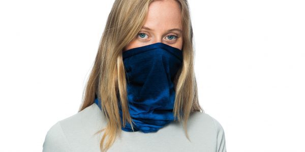 A studio landscape shot of a young woman wearing a Wool Buff® as face mask. She is blond, wearing a white shirt & standing in front of a white background. The tye-died blue Wool Buff® stands out. Source: buff.eu © Distributed for the promotion of the Wool Buff®