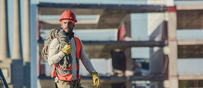 Photo of a male construction worker wearing a Buff® Professional Thermal Hat under his hard hat. The colours indicate that it is cold on site. In the background you can see a multi story development in it's raw concrete state. Source: buff.eu