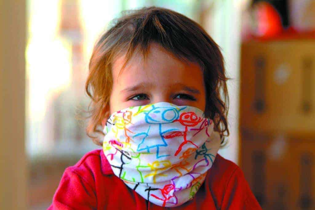 A toddler wearing a Baby Buff® as a face mask. The toddler looks happy. Source: buff.eu