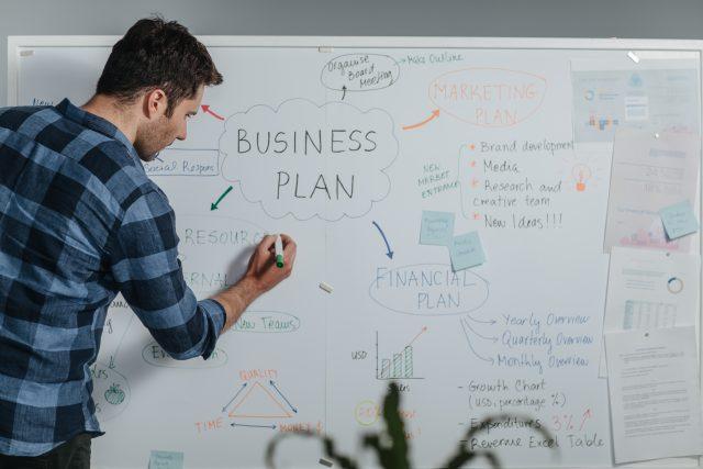 Muž stojící u podnikatelského plánu
