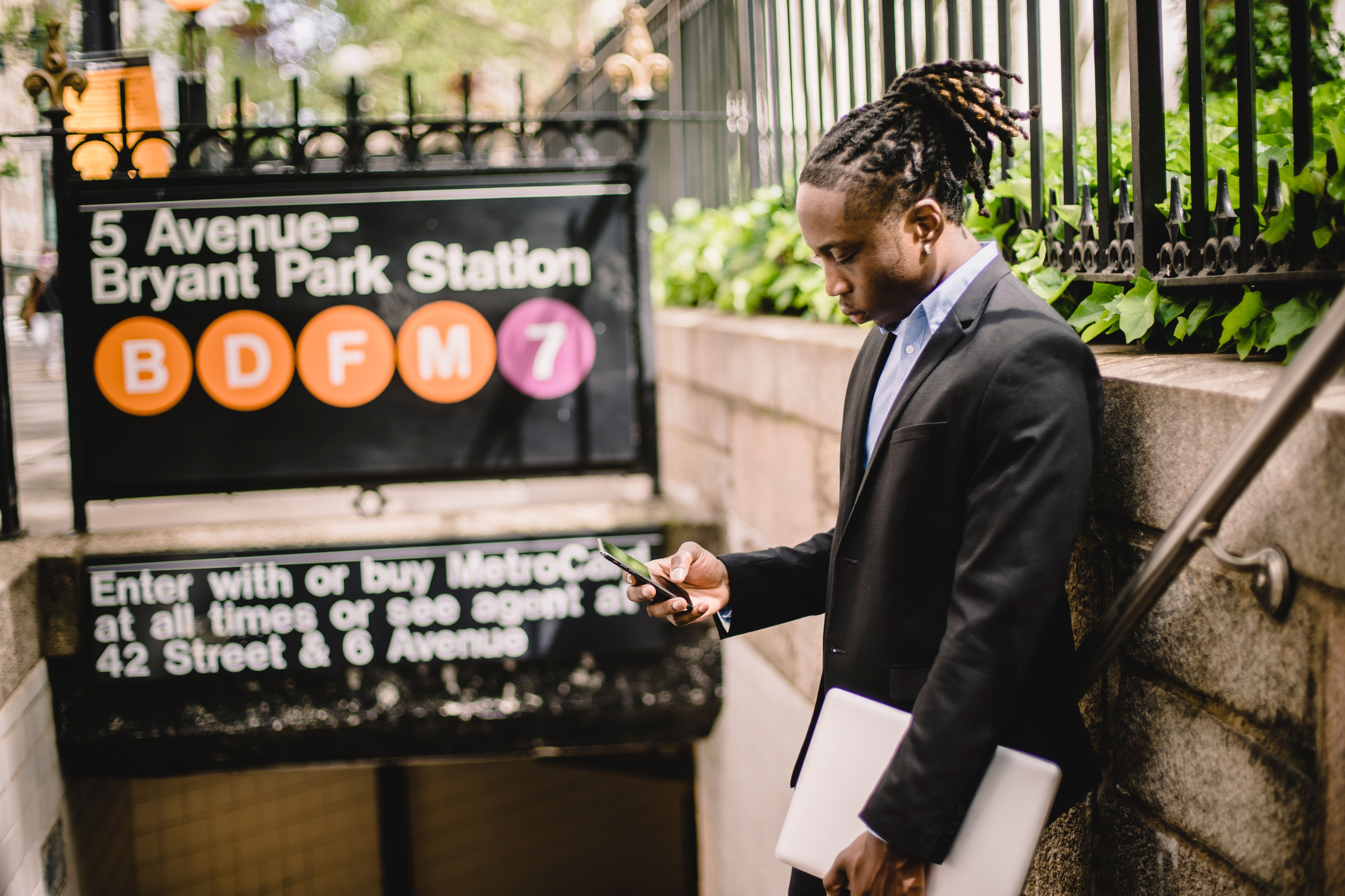 A man in a suit stands outside the entrance to the 5th Avenue Bryant Park Metro station in New York City, holding a closed laptop at his side and in his left hand, while he browses his smartphone with his right hand.