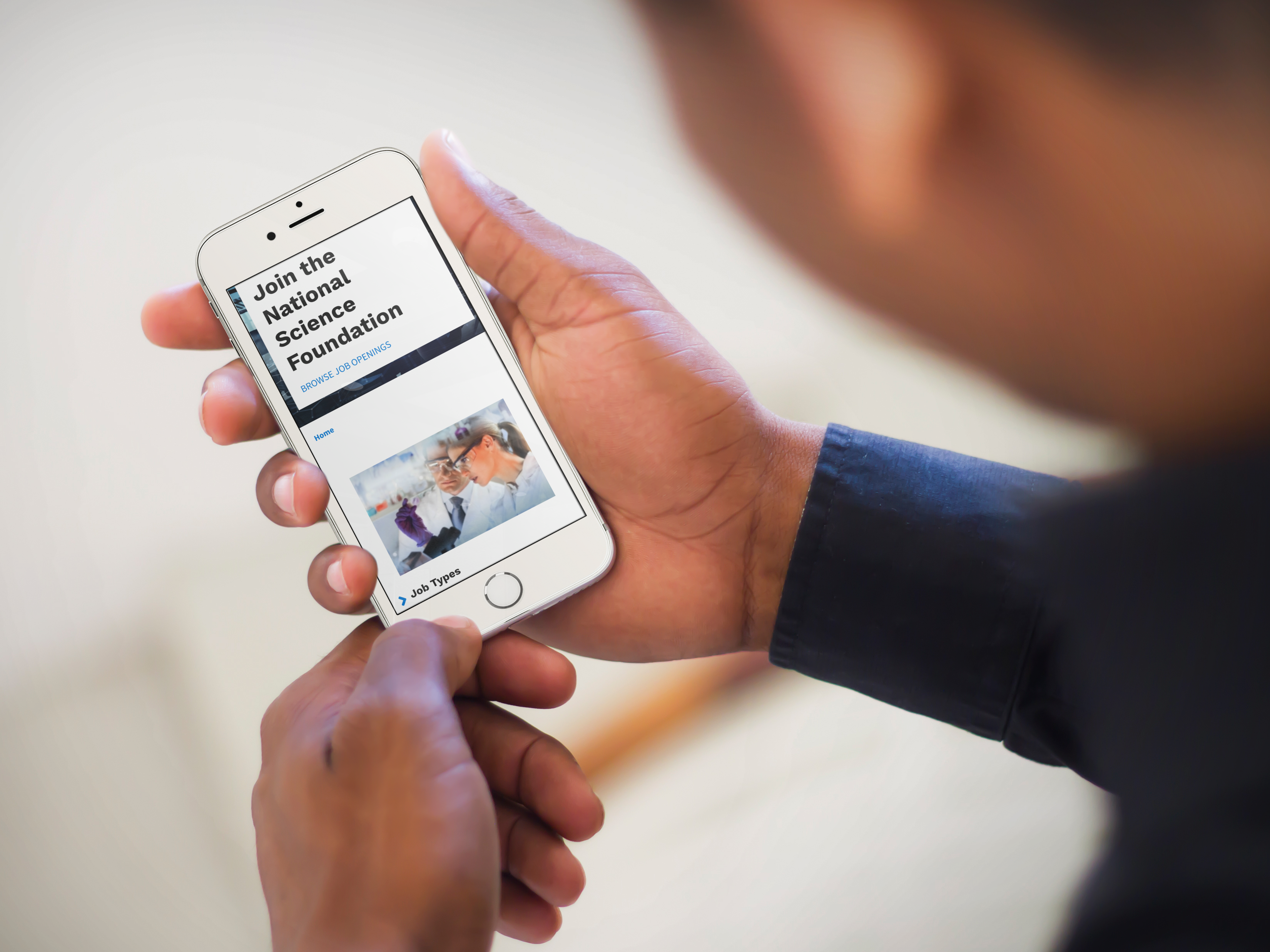 A person viewing NSF career opportunities on a mobile device.