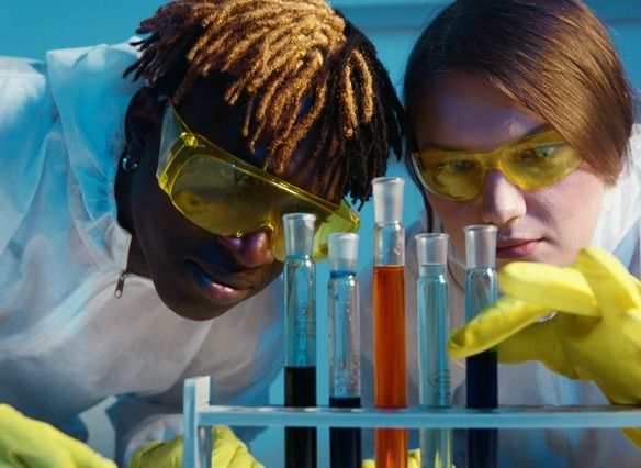 A man and a woman wearing protective wear look through goggles at a number of test tubes with different colored liquids.