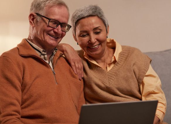 Older couple looking at a laptop to access medical benefits information.
