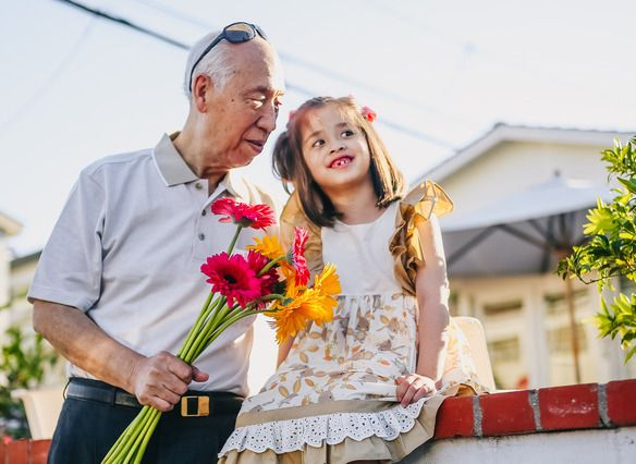An older gentleman holds a bouquet of flowers in his right hand, while his left hand circles the waist of a young girl next to him who is presumably his granddaughter.