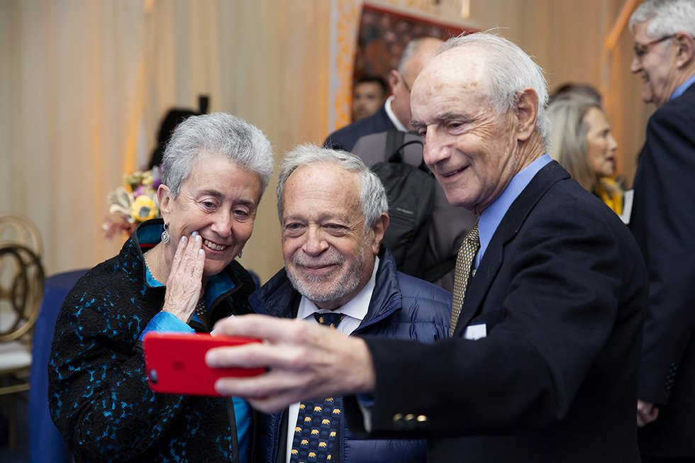 Photo of two guests taking a selfie with Robert Reich