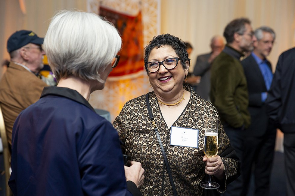 Photo of two women in conversation; the one facing the camera smiles and holds a glass of champagne