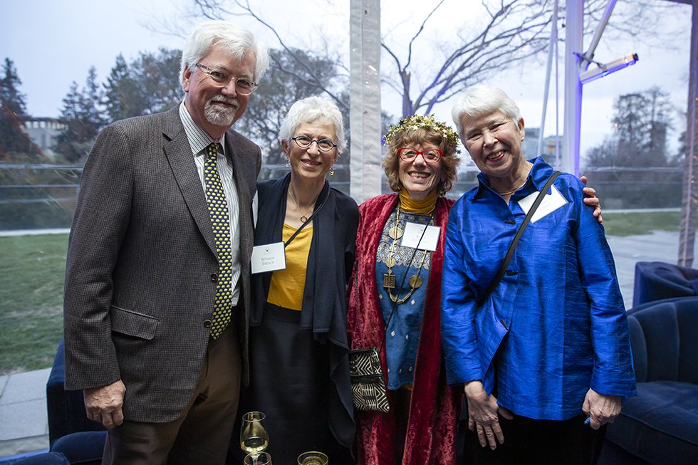Photo of Chancellor Christ smiling and facing camera with three smiling guests in a sunlit part of the reception tent