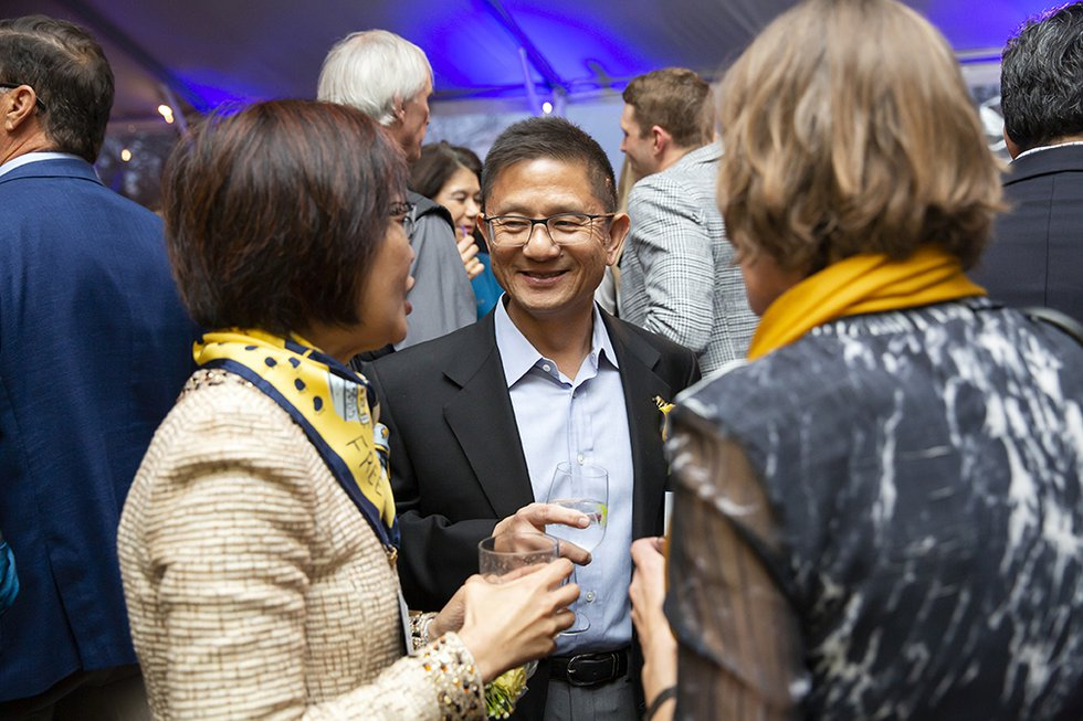 Photo of a smiling guest facing the camera, in conversation with two women facing him