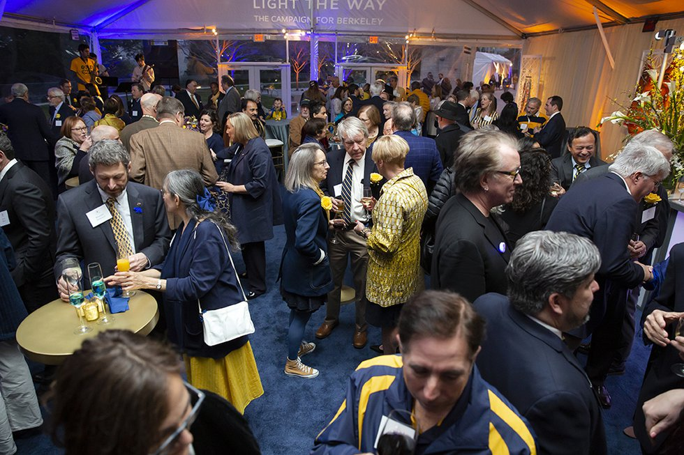 Photo of a festive event tent full of guests, many dressed in blue and gold