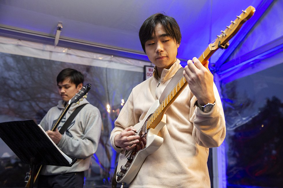 Photo of two student musicians playing, guitarist in the foreground and bassist in the background