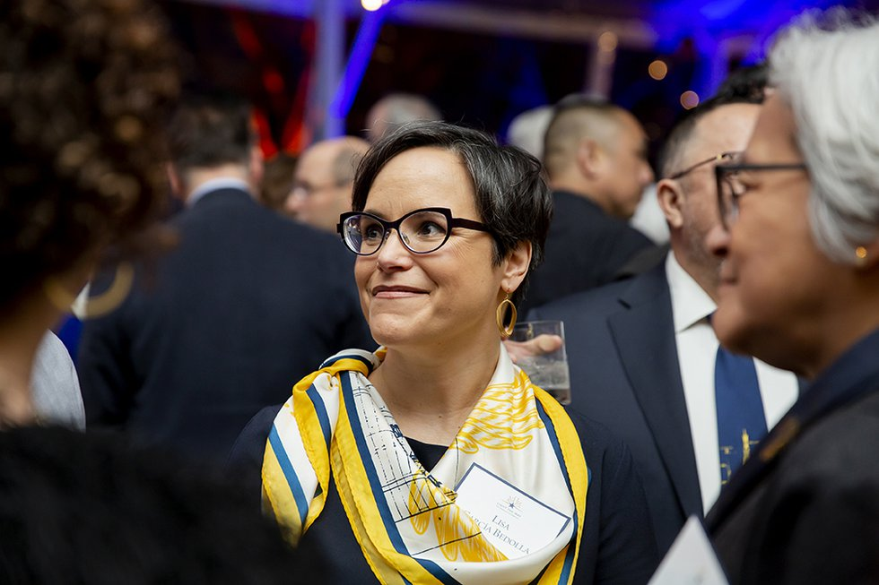 Photo of Vice Provost for Graduate Studies and Dean of the Graduate Division Lisa García Bedolla wearing a blue and gold scarf and smiling at something off-camera