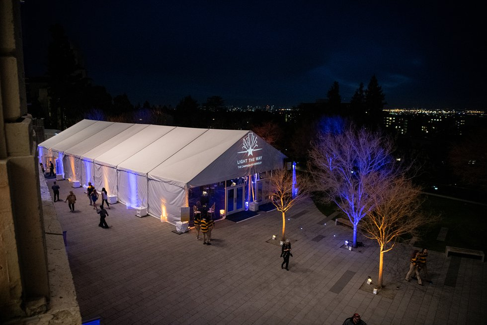Photo of the reception tent from above, lit festively with blue and gold lights