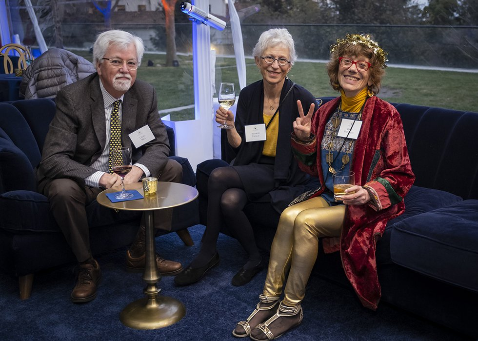 Photo of three guests seated, smiling into camera, one flashing a peace sign with her fingers