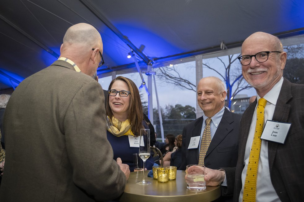 Photo of Vice Chancellor Julie Hooper in conversation with two guests while one other looks into the camera, smiling
