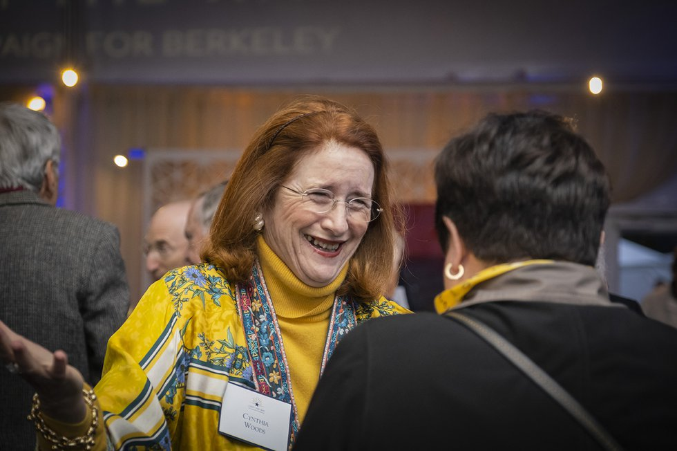 Photo of a guest wearing bright gold and blue, smiling in conversation