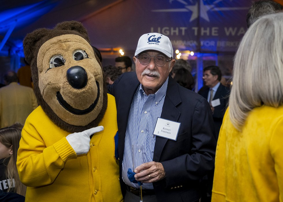 Photo of Oski posing with and pointing to a guest wearing a Cal Rowing hat