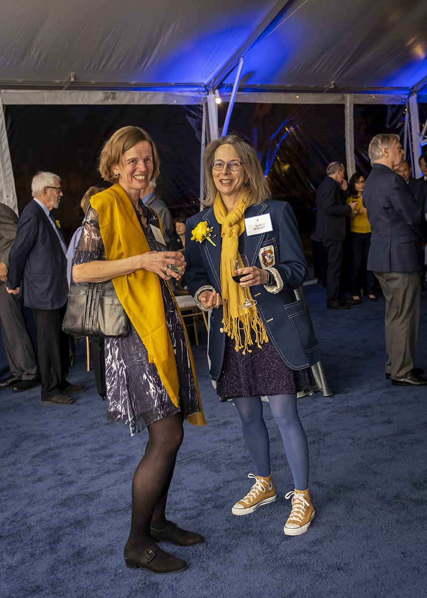 Photo of two guests in festive blue and gold, standing and smiling into the camera