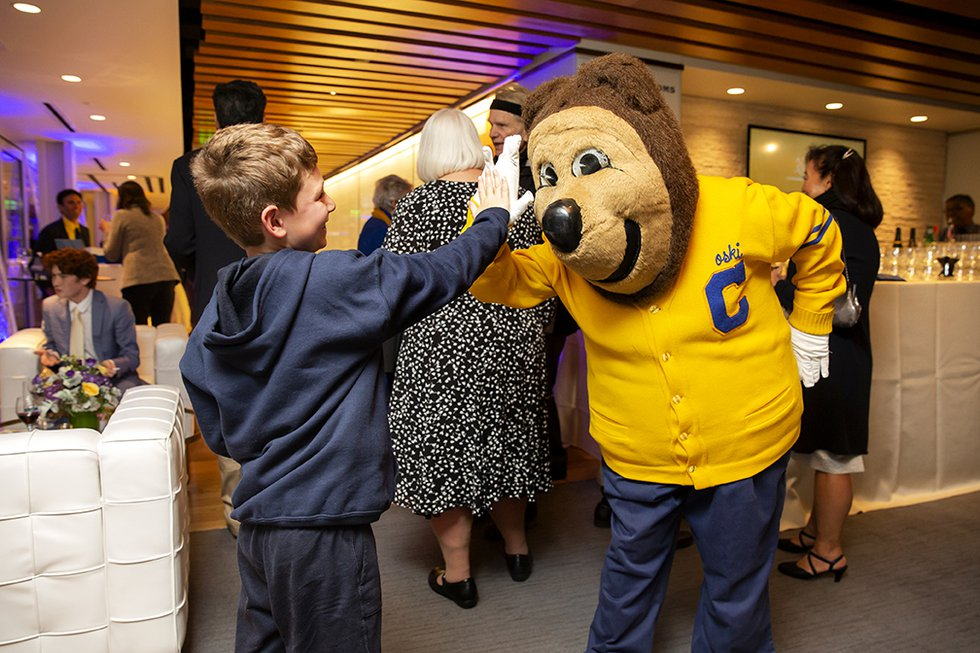 Photo of Oski giving a high-five to a small boy.