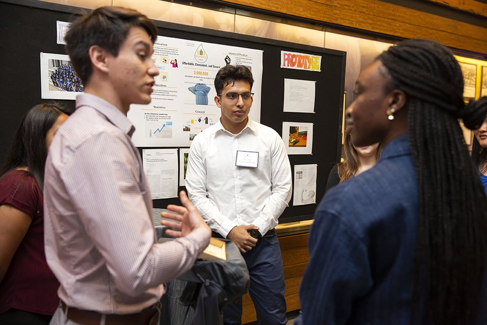 Photo of guests and researchers talking near a display of their scientific work