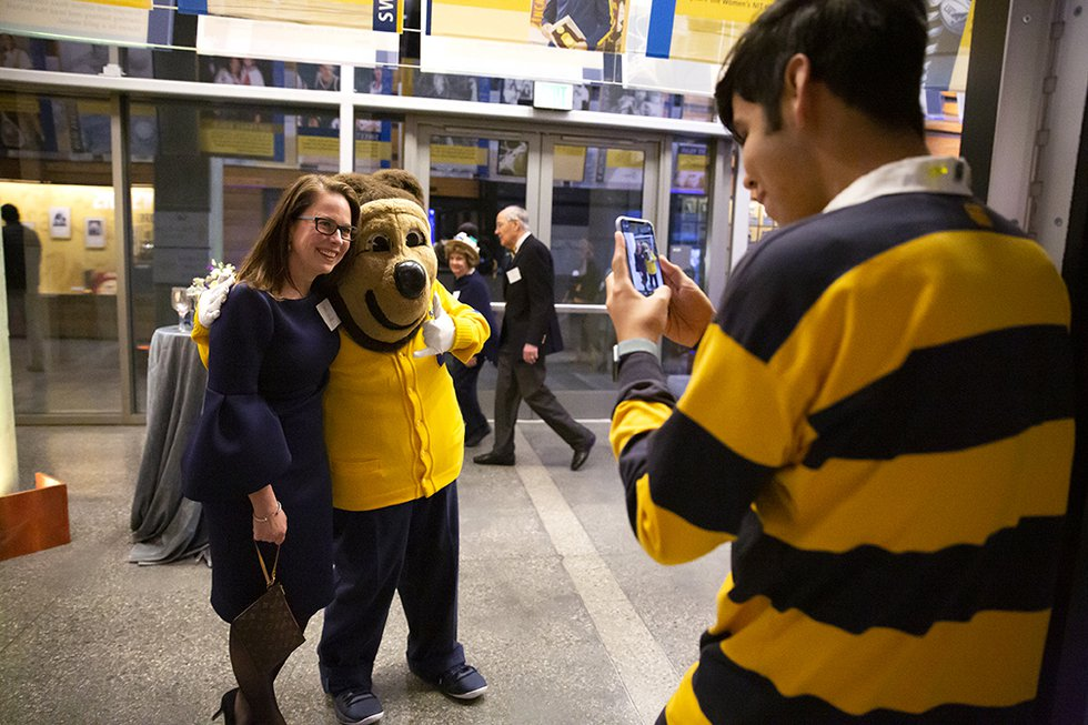 Photo of a Rally Comm student taking a picture of Oski with Vice Chancellor for University Development and Alumni Relations Julie Hooper