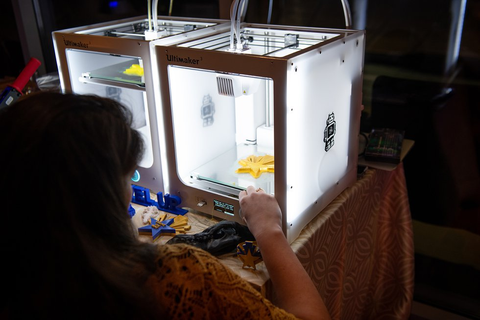 Photo of a 3-D printer lit up, with a guest in shadow facing it