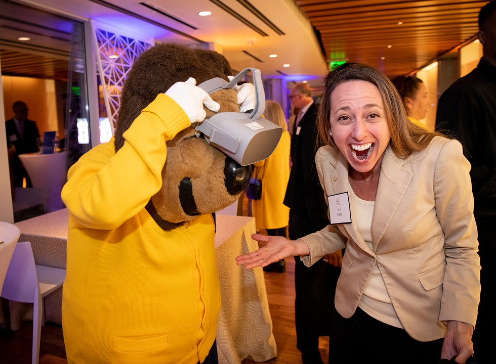 Photo of Oski looking through a virtual reality headset while Amy Herr smiles enthusiastically at the camera