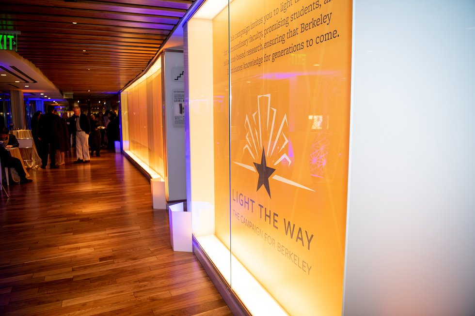"Photo of the hallway at the University Club, focused on a gold banner on the wall with the ""Light the Way"" logo"
