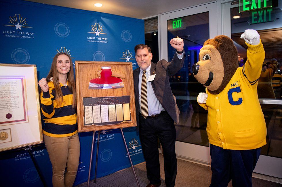 Photo of Vice Chancellor for Student Affairs Steve Sutton posing with the Stanford Axe alongside a Rally Comm student and Oski