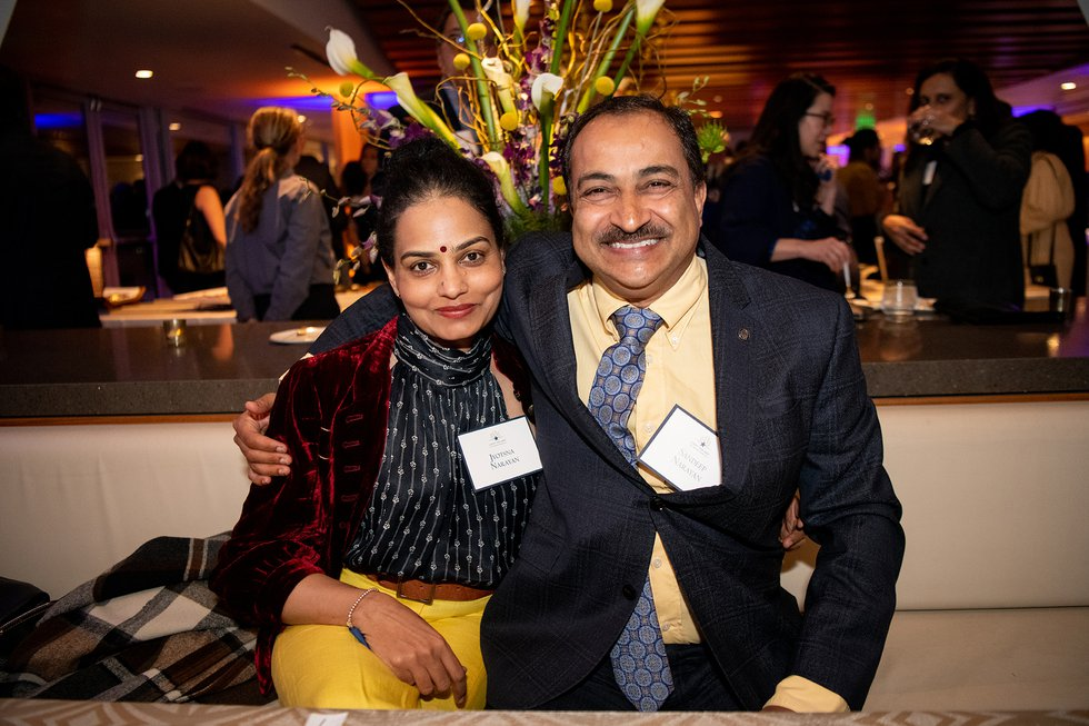 Photo of Jyotsna and Sandeep Narayan sitting together, smiling into the camera