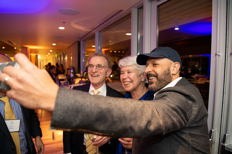 Photo of Maz Jobrani taking a selfie with Chancellor Christ and Randy Schekman