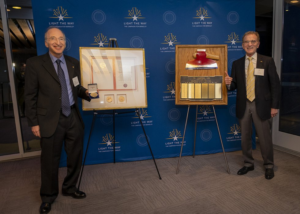 Photo of  Nobel Laureates Saul Perlmutter and Randy Schekman posing with Nobel prizes and the Stanford Axe