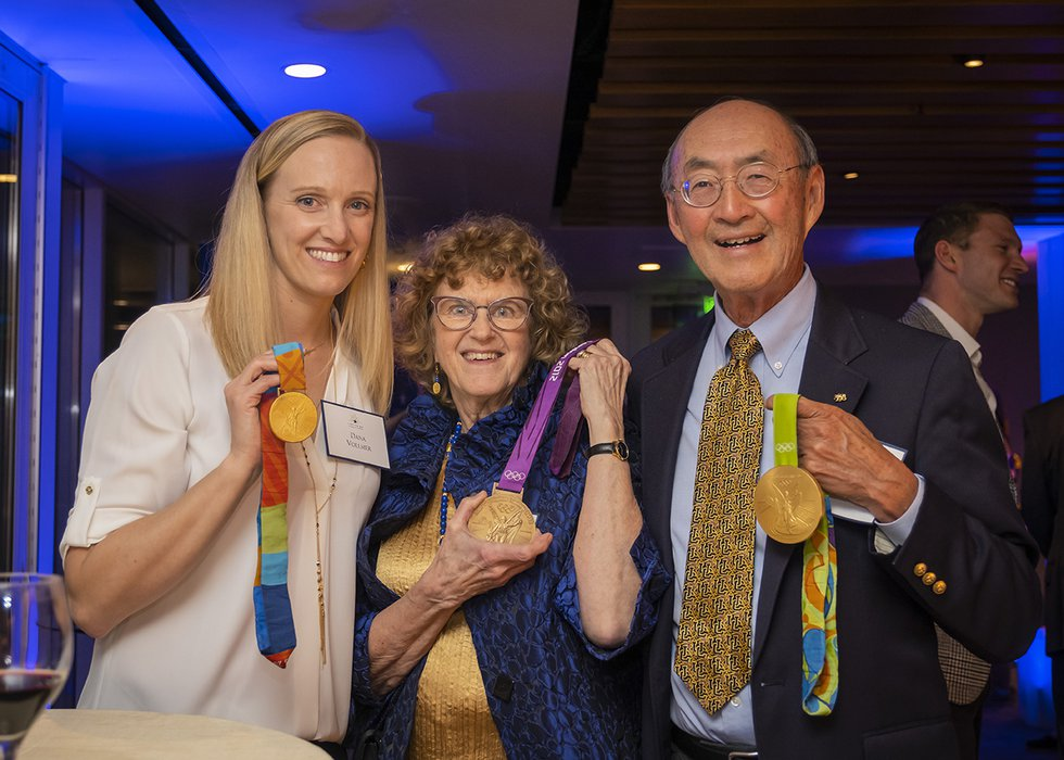 Photo of Dana Vollmer posing with two guests, all holding Olympic medals