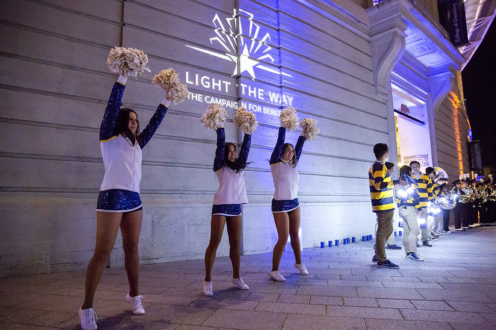 "Photo of members of the Berkeley Dance Team perform outside, in front of a projection of the ""Light the Way"" logo, with members of Rally Comm cheering off to the side"