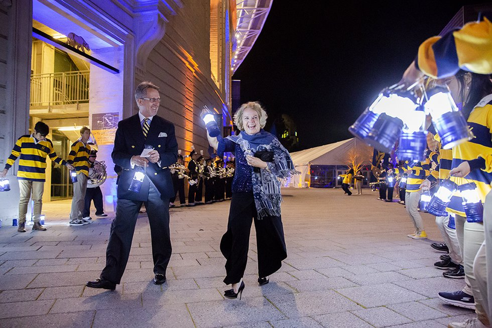 Photo of two guests walking outside the stadium, holding lit lanterns, flanked by cheering Rally Comm students also holding lanterns