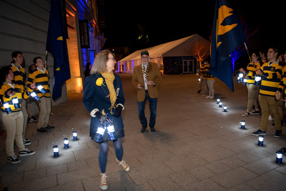 Photo of smiling guests receiving lit lanterns from Rally Committee as they leave the event