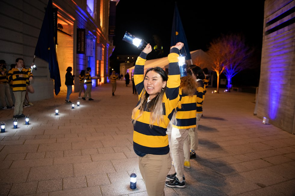Photo of a smiling Rally Committee member, her arms above her head, a lit lantern in each hand