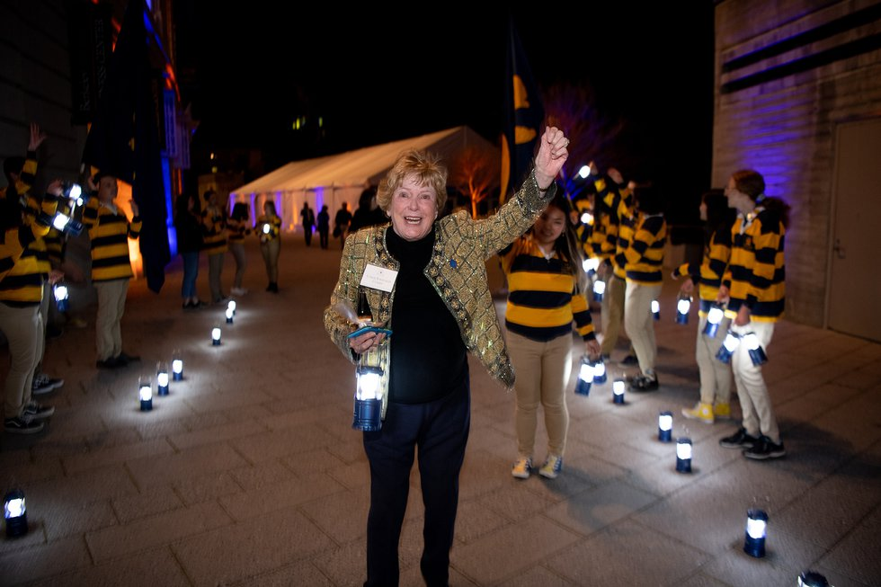 Photo of Carole Kavanaugh Clarke, wearing a glittering gold jacket, cheering with one hand in the air, the other holding a lantern as she leaves the event, Rally Comm members on either side of her