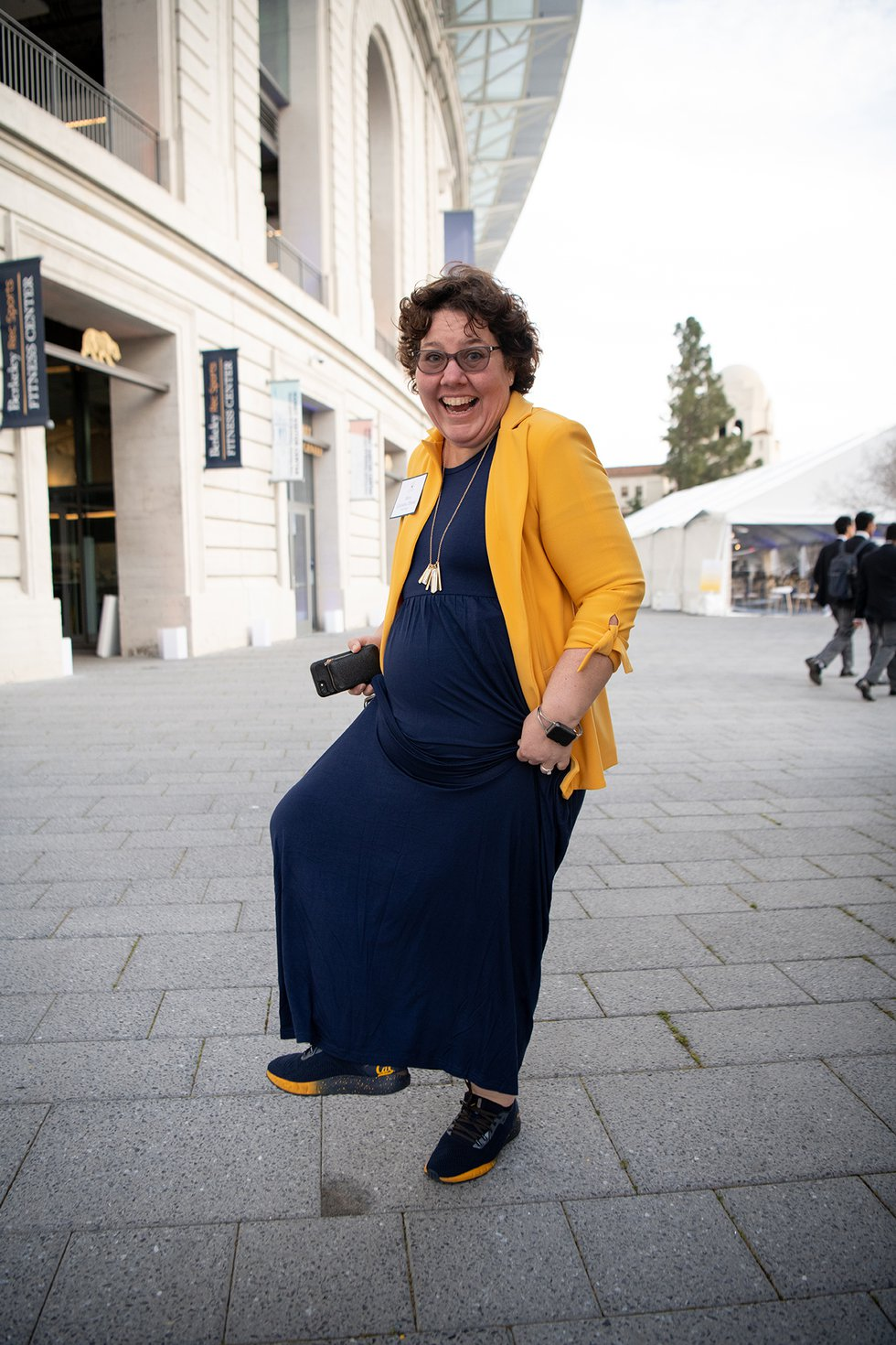Photo of a woman in a blue dress and gold blazer, smiling at the camera and dancing