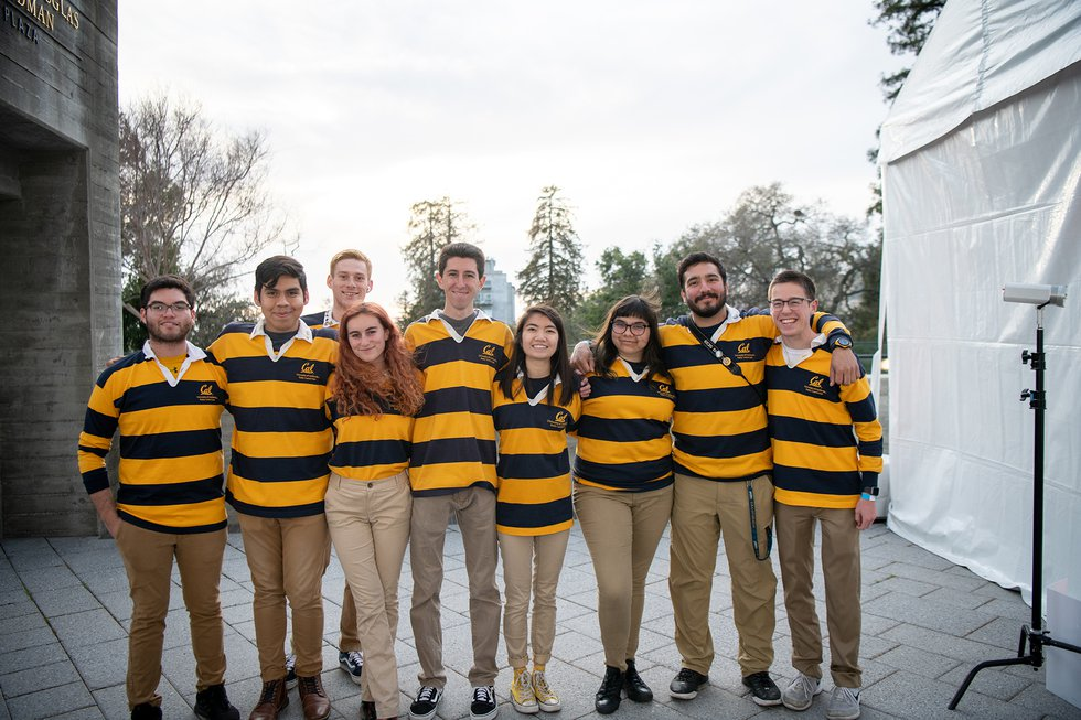 Photo of nine students in striped Rally Committee rugbys, standing with arms around each other's shoulders and smiling at the camera